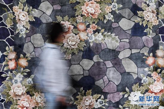 一名参观者从天水丝毯前走过(4月12日摄)。新华社记者 陈斌 摄