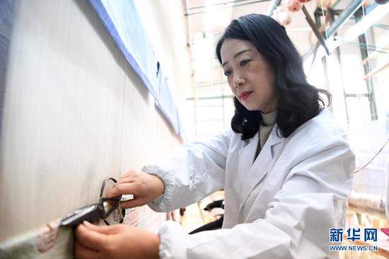 黄晶蓉在天水丝毯织造车间里编织丝毯(4月12日摄)。新华社记者 杜哲宇 摄