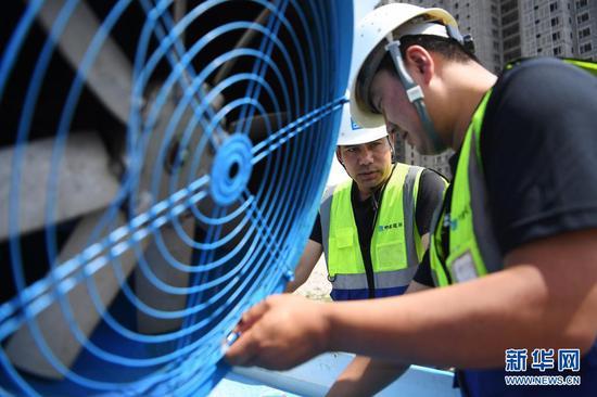 在甘肃省兰州市中建三局一处建设工地上,技术人员调试使用循环再生水的雾炮机(5月12日摄)。新华社记者 陈斌 摄