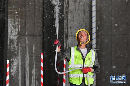 在甘肃省兰州市中建三局一处建设工地上,一名工人使用循环再生水施工作业(5月12日摄)。新华社记者 陈斌 摄