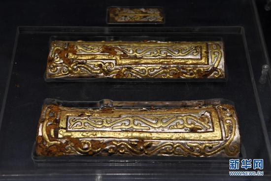 出土于马家塬西戎墓葬的铁鋄金银车后锺饰(5月18日摄)。新华社记者 范培珅 摄