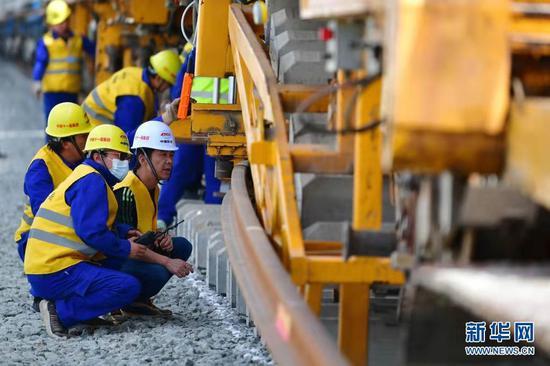 5月30日,中铁十一局建设者在中兰客专甘肃段铺轨施工现场作业。 新华社记者 陈斌 摄