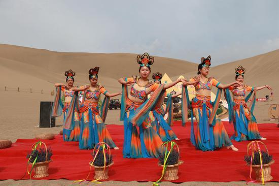 2021年6月13日,在甘肃省敦煌市鸣沙山月牙泉景区,景区工作人员为游客表演敦煌舞。