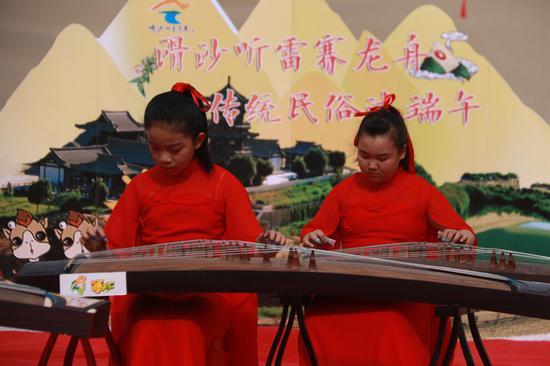 2021年6月13日,小朋友在甘肃省敦煌市鸣沙山月牙泉景区弹奏古筝。