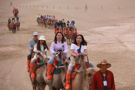 2021年6月13日,游客骑骆驼在甘肃省敦煌市鸣沙山月牙泉景区游览。