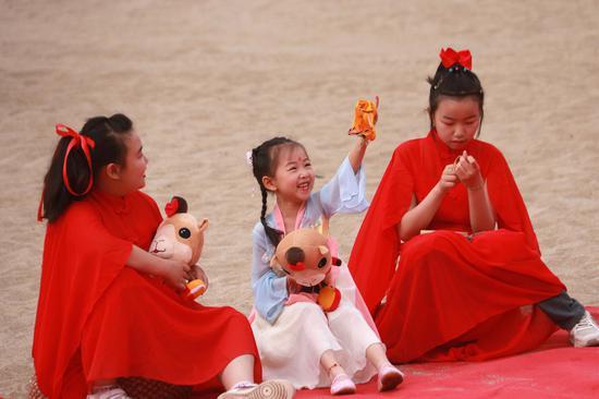2021年6月13日,小朋友在甘肃省敦煌市鸣沙山月牙泉景区玩耍。