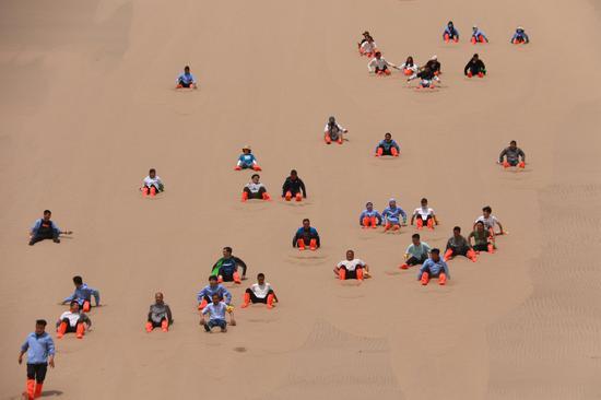 2021年6月13日,市民游客在甘肃省敦煌市鸣沙山月牙泉景区滑沙。