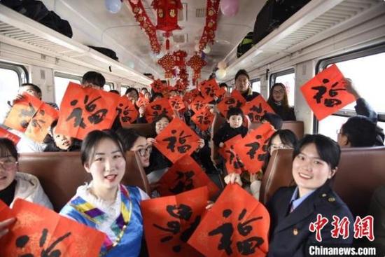 """图为""""慢火车""""上的乘客和乘务员高举""""福""""字,感悟浓浓""""年味"""""""