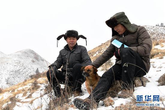 """1月15日,三岔资源管护站护林员冯德俊(右)、张得团在巡山途中和""""小黄""""一起休息。"""