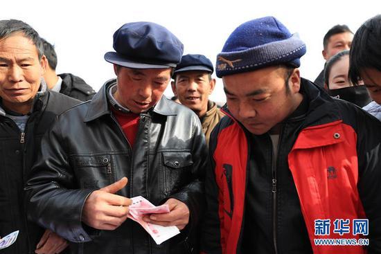 1月20日,在元古堆村2019年度企业带动入股分红大会上,村民在清点领到的分红。