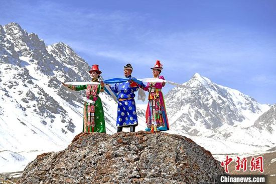 图为4月中旬,裕固族民众身着民族服装在巴尔斯雪山下。