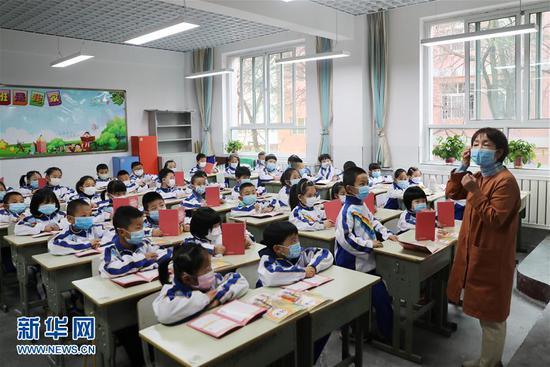 4月23日,在兰州市七里河区七里河小学,老师教一年级学生如何正确佩戴口罩。