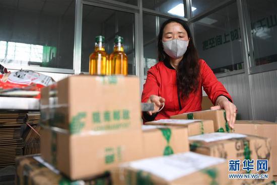 梁倩娟将客户订购的农产品打包,准备快递发运(3月8日摄)。新华社记者 陈斌 摄