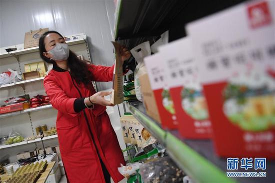 梁倩娟在自己的电商服务点整理货架上的农产品(3月8日摄)。新华社记者 陈斌 摄