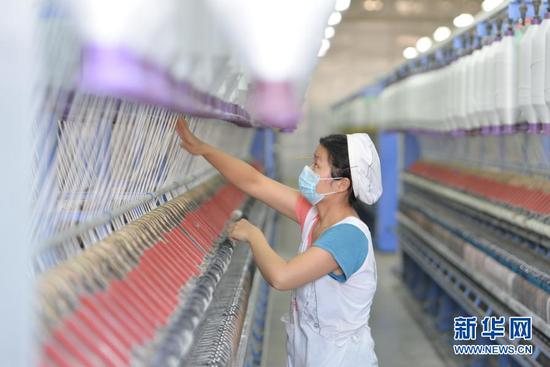 1月5日,工人在甘肃省临夏回族自治州东乡族自治县达板镇一纺织扶贫车间内作业。新华社发(史有东 摄)