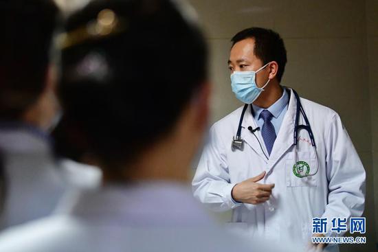 曹云山和年轻医生交流(1月13日摄)。新华社记者 陈斌 摄