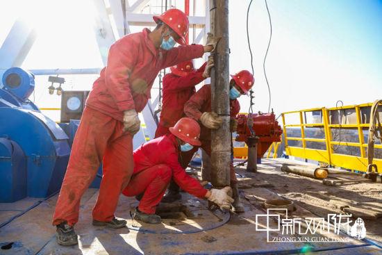 图为开钻现场采油二厂操作人员齐心协力调整大小。 杨军平 摄