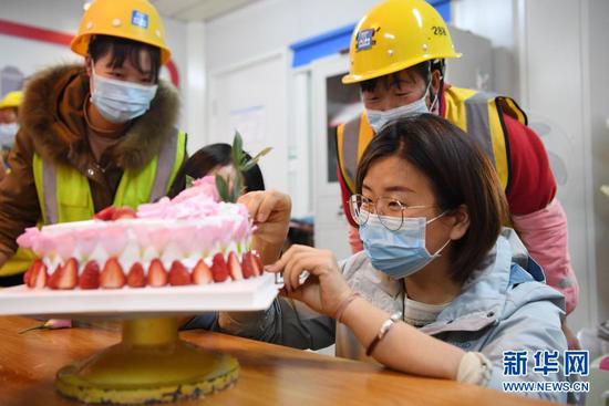 """杜萱(右一)和女工友一起在工地上制作蛋糕庆祝""""三八""""妇女节(3月4日摄)。新华社记者 杜哲宇 摄"""