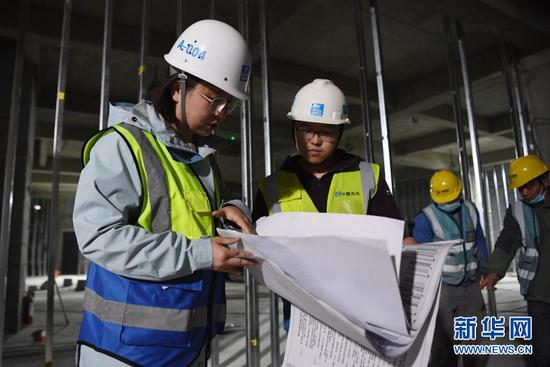 杜萱(左一)在甘肃省妇女儿童医疗综合体项目三标段工地上查看技术图纸(3月4日摄)。新华社记者 杜哲宇 摄