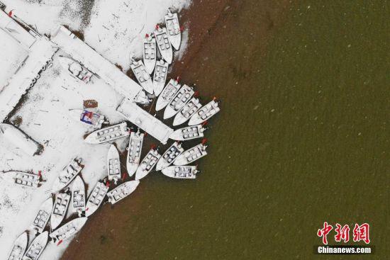 图为兰州黄河岸边的船只被白雪覆盖。(无人机照片) 中新社记者 高展 摄