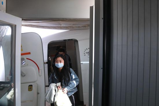 3月28日,东航武汉--银川--敦煌首航航班降落在甘肃敦煌莫高国际机场,旅客走出机舱。
