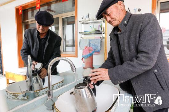 图为古浪县干城乡富民新村村民徐生喜正在接自来水。
