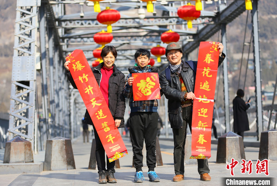 2021年春节期间,台湾夫妻杜书亿和王梅芬带着孩子一起在兰州中山铁桥前合影留念。中新社记者 高展 摄