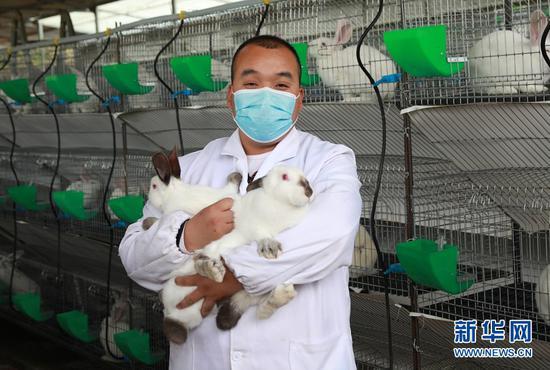 周鹏抱着自己的兔子。新华网发(张平良 摄)