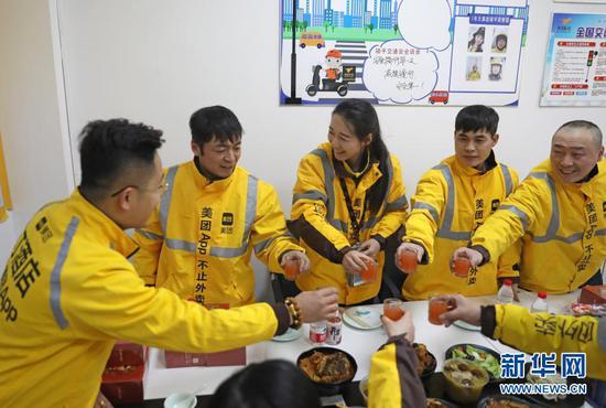 2月10日 ,美团专送骑手小月月(中)和同事在配送站点聚餐过年。新华社记者 杨青摄