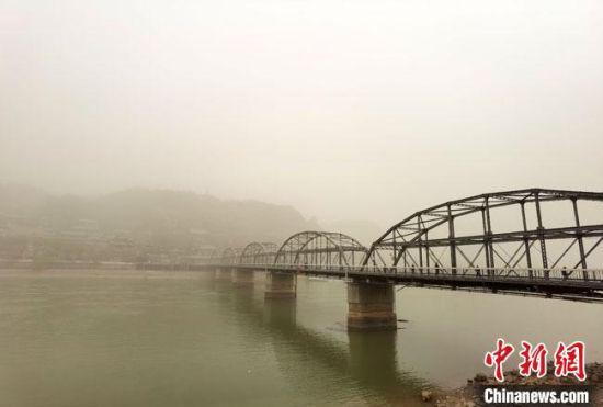 """3月16日,甘肃省会兰州被滚滚沙尘笼罩,天地一片昏黄的空气里""""沙尘迷眼,土味呛人""""。图为200余米的""""天下黄河第一桥""""兰州中山桥""""见首难见尾""""。 冯志军 摄"""