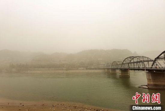 """从3月16日0时起,此前持续受沙尘天气影响的兰州市,空气质量指数持续""""爆表"""",市区最低能见度仅为500米。图为16日傍晚,兰州黄河铁桥被浮尘笼罩。 冯志军 摄"""