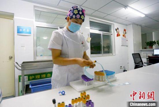 5月10日,支援武汉归来的甘肃庆阳市人民医院血液科护士袁文华正在贴化验单。