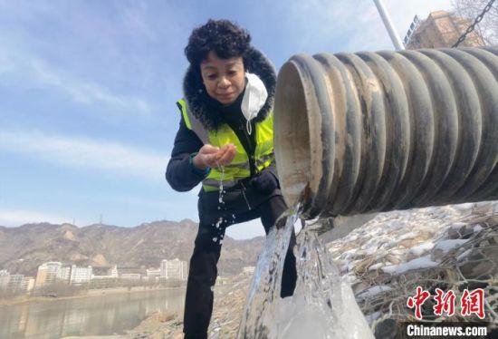 图为管道疏浚工刘英检查雨水管道口是否通畅,水体是否有异味。 杨艳敏 摄