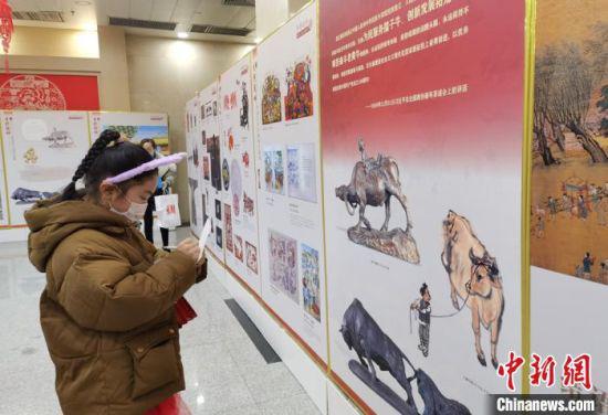 图为今年9岁的李蕊涓驻足于生肖文物联展前,用随身携带的纸笔做学习记录。 张婧 摄