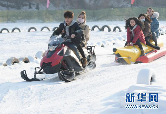 2021年1月1日,在甘肃省临夏回族自治州临夏市南龙镇金色草滩景区,游客乘坐雪地车。新华社发(史有东 摄)