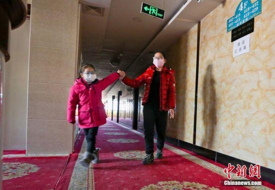 """图为甘肃张掖首批湖北籍游客""""解禁""""第一天,湖北籍游客与女儿高兴的在楼道里散步。"""