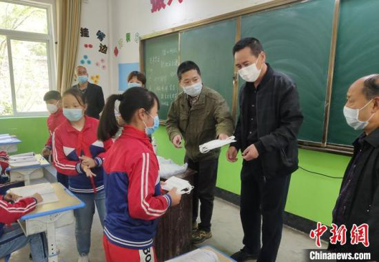 图为冯继(右三)和老师给学生发放防疫物资。(资料图)受访者供图
