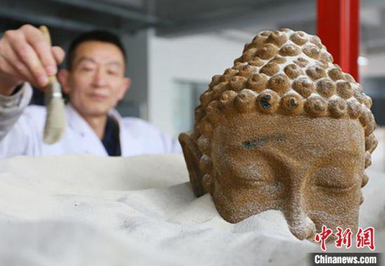 """4月初,位于兰州高新区的甘肃伯骊江3D打印科技有限公司内,56岁的""""玩""""沙人潘炳庆清理由沙子打印成的佛像模型。 高展 摄"""