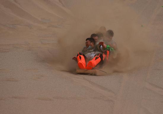 2021年6月13日,在甘肃省敦煌市鸣沙山月牙泉景区,选手在参加划旱龙舟比赛。