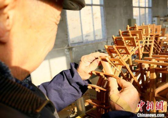 图为段怡村正在进行黄河水车制作。