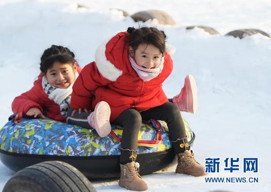 2021年1月1日,在甘肃省临夏回族自治州临夏市南龙镇金色草滩景区,小朋友在滑雪圈。新华社发(史有东 摄)