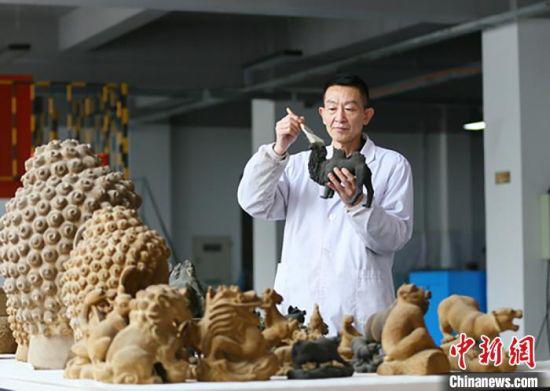 图为潘炳庆和仿制文物及文创产品的合影。 高展 摄