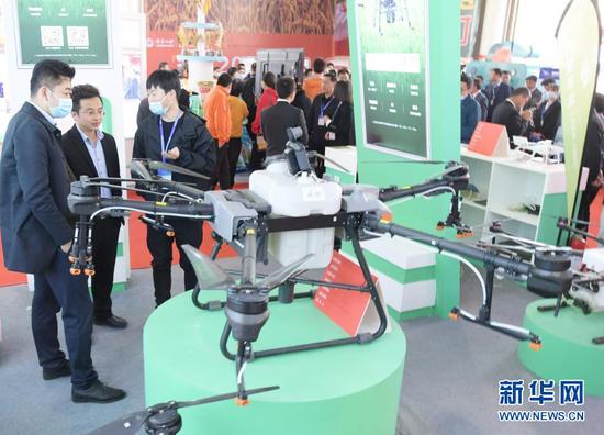 在临夏州举行的现代农业机械展示展销活动上,观众在参观喷药无人机(3月12日摄)。新华社发(史有东 摄)