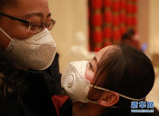 2月4日,甘肃省第二人民医院骨科主管护师谭锦柯(右)在出发前和丈夫王海默告别,王海默也是甘肃省第二人民医院的一位医生。