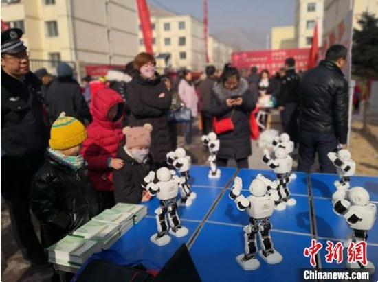 图为七里河区科技局带来的机器人表演吸引小朋友观看。