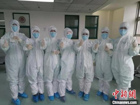图为穿戴严实的甘肃陇南市援助武汉医疗队互相鼓励、加油打气。
