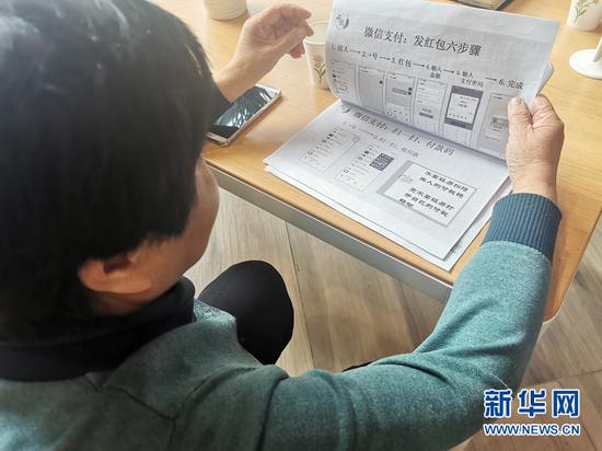 郑辉芳在翻看有关智能手机使用的教材。新华社记者 何问 摄