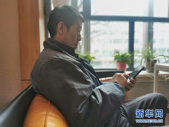 尹春元在使用智能手机。新华社记者 何问 摄