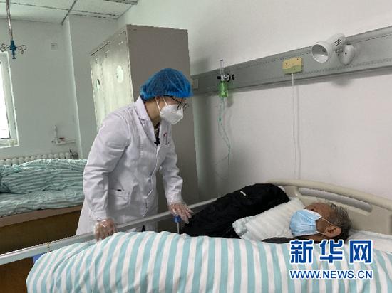 张荣霞(左)在白银市中西医结合医院感染科与住院患者交流(新华社记者 程楠 摄)
