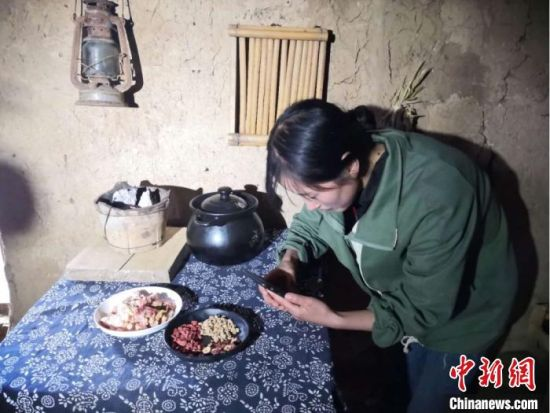 """图为宕昌磨河坝村农家女,用手机录制烹饪""""山味""""的视频,与生活在都市的网友们分享。"""